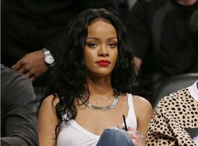 FILE - This April 25, 2014 file photo shows singer Rihanna watching Game 3 of an NBA basketball first-round playoff series between the Brooklyn Nets and the Toronto Raptors in New York. CBS said Tuesday, Sept. 16, 2014 it was permanently editing a song featuring Rihanna's voice out of its Thursday night NFL telecasts _ after the singer issued a profane tweet about it. A portion of Jay-Z's