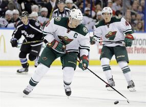 Minnesota Wild center Mikko Koivu (9), of Finland, tries to control the puck as he enters the Tampa Bay Lightning zone during the first period of an NHL hockey game Saturday, Nov. 22, 2014, in Tampa, Fla. (AP Photo/Chris O'Meara)