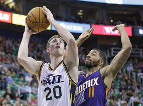 Utah Jazz's Gordon Hayward (20) goes to the basket as Phoenix Suns' Markieff Morris (11) defends during the fourth quarter of an NBA preseason basketball game Friday, Oct. 24, 2014, in Salt Lake City. The Suns won 105-100. (AP Photo/Rick Bowmer)