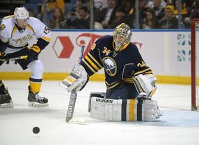 Nashville Predators center Craig Smith (15) battles for a loose puck in front of Buffalo Sabres goaltender Michal Neuvirth (34) during the second period of an NHL hockey game Sunday, Feb. 22, 2015, in Buffalo, N.Y. The New York Islanders have acquired goalie Neuvirth from the Buffalo Sabres for goaltender Chad Johnson and a 2016 third-round pick. THE CANADIAN PRESS/ AP/Gary Wiepert