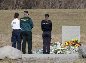 Spanish police officers pay tribute next to a stele and flowers laid in memory of the victims in the area where the Germanwings jetliner crashed in Le Vernet, France, Friday, March 27, 2015. Germanwings co-pilot Andreas Lubitz appears to have hidden evidence of an illness from his employers, including having been excused by a doctor from work on Tuesday, the day authorities say he crashed a passenger plane into a mountain, prosecutors said. (AP Photo/Claude Paris)