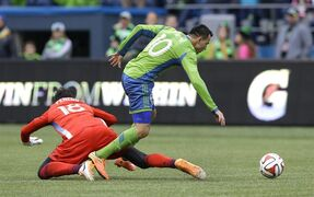 Seattle Sounders midfielder Marco Pappa, right, breaks away after winning the ball from Los Angeles Galaxy goalkeeper Jaime Penedo, left, in the second of an MLS soccer match, Saturday, Oct. 25, 2014, in Seattle. Pappa scored on the play, giving the Sounders a 2-0 win over the Galaxy. (AP Photo/Ted S. Warren)