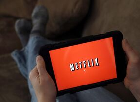 A person displays Netflix on a tablet in North Andover, Mass., Jan.17, 2014. Experts say a move by Netflix to defy the will of Canada's broadcast regulator calls into question its very authority to institute any rules governing Internet-based video service providers. THE CANADIAN PRESS/AP/Elise Amendola