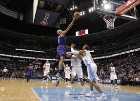 Charlotte Hornets guard Gerald Henderson, left, jumps over Denver Nuggets forward Wilson Chandler, back right, and guard Arron Afflalo for a basket in the first quarter of an NBA basketball game Saturday, Jan. 31, 2015, in Denver. (AP Photo/David Zalubowski)