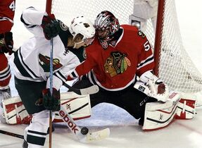 Chicago Blackhawks goalie Corey Crawford, right, blocks a shot by Minnesota Wild center Mikael Granlund during the third period of Game 1 in the second round of the NHL Stanley Cup hockey playoffs in Chicago, Friday, May 1, 2015. (AP Photo/Nam Y. Huh)