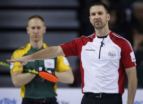 Newfoundland and Labrador skip Brad Gushue, right, gestures to his teammates as Northern Ontario skip Brad Jacobs looks on during curling action at the Brier in Calgary, Thursday, March 5, 2015.THE CANADIAN PRESS/Jeff McIntosh