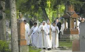 Anglican clerics lead a procession through St. John's Cemetery following a smudging ceremony.