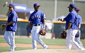 Seattle Seahawks quarterback Russell Wilson, center, has a laugh listening to Texas Rangers first baseman Prince Fielder, front right, prior to a Rangers spring training baseball game against the San Diego Padres Saturday, March 28, 2015, in Surprise, Ariz. (AP Photo/Lenny Ignelzi)
