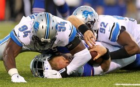 Buffalo Bills quarterback Jordan Palmer, bottom, loses his helmet while being brought down by Detroit Lions defensive ends Devin Taylor (92) and Ezekiel Ansah (94) during the first half of a preseason NFL football game, Thursday, Aug. 28, 2014, in Orchard Park, N.Y. (AP Photo/Bill Wippert)