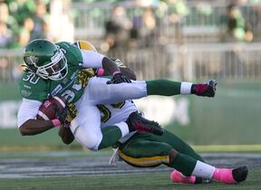 Saskatchewan Roughriders running back Will Ford is tackled by Edmonton Eskimos linebacker Rennie Curran during the second quarter of CFL football action in Regina, Sask., Sunday, October 19, 2014. THE CANADIAN PRESS/Liam Richards