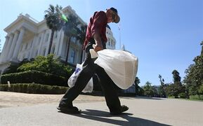 FILE -- In this Aug. 12, 2014, file photo plastic single-use bags are carried past the state Capitol in Sacramento, Calif. Gov Jerry Brown signed SB270 by Sen. Alex Padilla, D-Los Angeles, Tuesday, Sept. 30, 2014, which imposes the nation's first statewide ban on single-use plastic bag.(AP Photo/Rich Pedroncelli,file)
