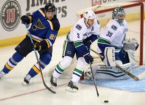 Vancouver Canucks goalie Ryan Miller (30) and teammate Kevin Bieksa (3) defend St. Louis Blues' Patrik Berglund (21), of Sweden, during the first period of an NHL hockey game, Thursday, Oct. 23, 2014, in St. Louis. (AP Photo/Bill Boyce)