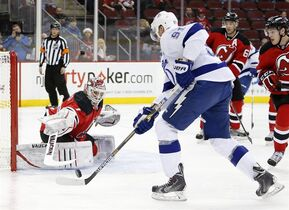 New Jersey Devils goalkeeper Keith Kinkaid, left, defends his net against Tampa Bay Lightning center Steven Stamkos during the first period of an NHL hockey game, Friday, Dec. 19, 2014, in Newark, N.J. (AP Photo/Julio Cortez)