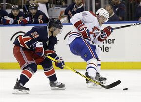 New York Rangers' Martin St. Louis, left, steals the puck from Montreal Canadiens' Alexei Emelin just before scoring during the second period of the NHL hockey game, Sunday, Nov. 23, 2014, in New York. (AP Photo/Seth Wenig)