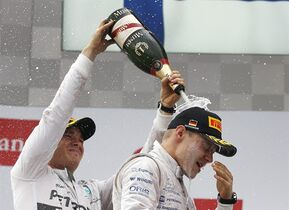 Mercedes driver Nico Rosberg of Germany, left, pours champagne over second place winner, Williams driver Valtteri Bottas of Finland, after winning the German Formula One Grand Prix in Hockenheim, Germany, Sunday, July 20, 2014. (AP Photo/Michael Probst)