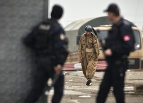 An Iraqi Kurdish peshmerga fighter walks at a staging area on the outskirts of Suruc, near the Turkey-Syria border, across from the Syrian town of Kobani, Thursday, Oct. 30, 2014. Ten Iraqi peshmerga fighters entered the northern Syrian border town of Kobani, also known as Ayn Arab, crossing over from Turkey on Thursday, the first from among a group of 150 Kurdish troops on their way into the embattled city.(AP Photo/Vadim Ghirda)