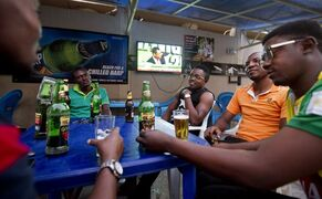 A group of Nigerian men drink beer and listen to television updates on the election results, at the Flexx Bush Bar and Lounge in the Sabon Gari neighborhood of Kano, Nigeria, Monday, March 30, 2015. Nigerians are waiting in hope and fear for results of the most tightly contested presidential election in the nation's turbulent history. (AP Photo/Ben Curtis)