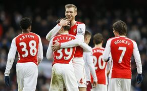 Arsenal's Hector Bellerin, centre, is hugged by captain Per Mertesacker after he scored their fifth goal during the English Premier League soccer match between Arsenal and Aston Villa at the Emirates stadium in London, Sunday, Feb. 1, 2015. (AP Photo/Kirsty Wigglesworth)