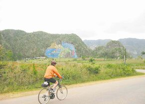 Doug Taylor, of Chelsea, Que., rides by the Prehistoric Mural symbolizing the theory of evolution, near Vinales. It is painted on a limestone cliff and took 15 people five years to complete.