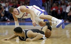 Los Angeles Clippers forward Blake Griffin, top, goers over the top of San Antonio Spurs guard Cory Joseph during the first half of Game 1 of a first-round NBA basketball playoff series in Los Angeles, Sunday, April 19, 2015. (AP Photo/Chris Carlson)