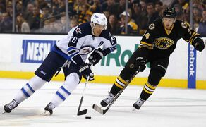 Winnipeg Jets' Blake Wheeler skates past Boston Bruins' Carl Soderberg, right, during the first period of an NHL hockey game in Boston Friday.