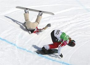 Lindsey Jacobellis of the United States crashes in the women's snowboard cross semifinal as Canada's Dominique Maltais. tries to avoid her at the Rosa Khutor Extreme Park, at the 2014 Winter Olympics, Sunday, Feb. 16, 2014, in Krasnaya Polyana, Russia. (AP Photo/Sergei Grits)