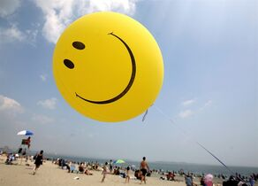 A smiley face balloon floats over Revere Beach in Revere, Mass. as beachgoers head for the water on Sunday, July 16, 2006. Researchers, government and the public are discussing hiking happiness at a Vancouver symposium. THE CANADIAN PRESS/AP/Michael Dwyer