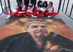 FILE - In this April 28, 2015 file photo, students read guides to Bogota's International Book Fair, as they sit next to a chalk painting of the late Colombian novelist Gabriel Garcia Marquez, in Bogota, Colombia. Colombian police are investigating the theft of a signed first edition of Garcia Marquez's novel,