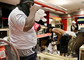 In this Aug. 10, 2014, photo by St. Louis Post-Dispatch photographer David Carson, a looter armed with a gun in his waistband steals items from a QuikTrip store after riots broke out at the end of a candlelight vigil for Michael Brown in Ferguson, Missouri. The store was later set afire. The St. Louis Post Dispatch photo staff are winners of the 2015 Pulitzer Prize for Breaking News Photography it was announced Monday, April 20, 2015, at Columbia University in New York. (David Carson, St. Louis Post Dispatch, Columbia University via AP)