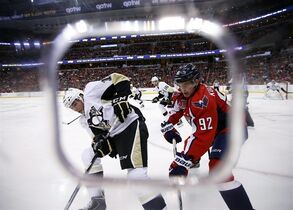 Pittsburgh Penguins right wing Beau Bennett (19) and Washington Capitals center Evgeny Kuznetsov (92), from Russia, battle for the puck against the boards, in the first period of an NHL hockey game, Wednesday, Jan. 28, 2015, in Washington. (AP Photo/Alex Brandon)