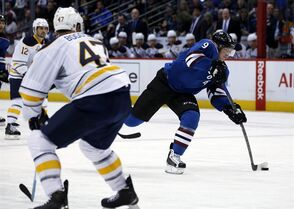 Colorado Avalanche center Matt Duchene, right, shoots for a goal after slipping between Buffalo Sabres right wing Brian Gionta, back left, and defenseman Zach Bogosian in the second period of an NHL hockey game Saturday, March 28, 2015, in Denver. (AP Photo/David Zalubowski)