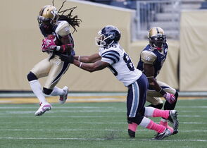 Winnipeg Blue Bombers' Alex Suber (21) snags the pass in front of Toronto Argonauts' Romby Bryant (80) during a 2013 game in Winnipeg. Suber is heading to Toronto in exchange for Argos defensive lineman Thaddeus Gibson.