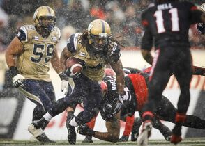 Winnipeg Blue Bombers Paris Cotton, centre, dodges Calgary Stampeders players during first half CFL football action in Calgary, Saturday, Nov. 1, 2014.