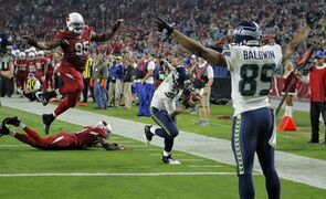 Seattle Seahawks quarterback Russell Wilson (3) runs in for a touchdown as teammate Doug Baldwin (89) signals touchdown as Arizona Cardinals defensive end Tommy Kelly (95) defends during the second half of an NFL football game, Sunday, Dec. 21, 2014, in Glendale, Ariz. (AP Photo/Rick Scuteri)