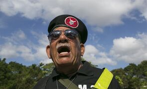 Vidal Martinez, former member of the Macho de Monte Division of the Panamanian Defense Forces, sings his national anthem during a ceremony in tribute to the victims of the U.S. invasion at a cemetery in Panama City, Saturday, Dec. 20, 2014. The U.S. intervention known as Just Cause began 25 years ago on Saturday, on Dec. 20, 1989, and ended with Noriega's surrender to American drug agents on Jan. 3. The invasion killed 314 Panamanian soldiers and 200 civilians, the government says, while the U.S. military reported losing 23 American soldiers. Local human rights organizations estimated that more than 1,000 Panamanians died. (AP Photo/Tito Herrera)