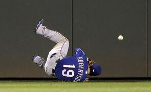 Texas Rangers center fielder Daniel Robertson tumbles while chasing a two-run double by Seattle Mariners' Endy Chavez in the fourth inning of a baseball game Tuesday, Aug. 26, 2014, in Seattle. (AP Photo/Elaine Thompson)