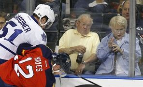 Fans react as Florida Panthers right wing Jimmy Hayes (12) checks Toronto Maple Leafs defenseman Jake Gardiner (51) during the first period of an NHL hockey game Sunday, Dec. 28, 2014, in Sunrise, Fla. (AP Photo/Terry Renna)