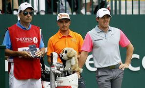 Rickie Fowler of the US, center, Rory McIlroy of Northern Ireland, right, and his caddie JP Fitzgerald wait to tee off the 1st during the final round of the British Open Golf championship at the Royal Liverpool golf club, Hoylake, England, Sunday July 20, 2014. (AP Photo/Peter Morrison)