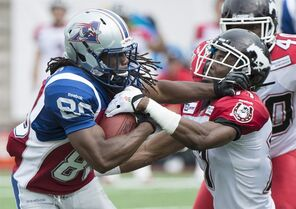 Montreal Alouettes' James Rodgers, left, fights off a tackle by Calgary Stampeders' Joshua Bell during first half CFL football action in Montreal, Sunday, September 21, 2014. THE CANADIAN PRESS/Graham Hughes