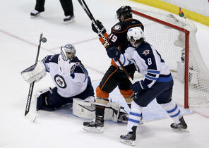Jets goalie Ondrej Pavelec blocks a shot as defenceman Jacob Trouba and  Ducks forward Patrick Maroon look for a rebound during first-period action.