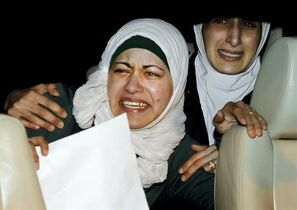 The sister, right, and wife, left, of Jordanian pilot, Lt. Muath al-Kaseasbeh, who is held by the Islamic State group militants, cry as they ride a car during a protest in front of the Royal Palace in Amman, Jordan, Wednesday, Jan. 28, 2015. Jordan on Wednesday offered a precedent-setting prisoner swap to the Islamic State group in a desperate attempt to save a Jordanian air force pilot the militants purportedly threatened to kill, along with a Japanese hostage. (AP Photo/Raad Adayleh)