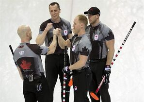Canada skip Brad Jacobs bumps fists with Ryan Fry (left), E.J.Harnden and Ryan Harnden (right) after defeating China 10-6 during semi-final curling action at the Sochi Winter Olympics Wednesday February 19, 2014 in Sochi, Russia. THE CANADIAN PRESS/Adrian Wyld
