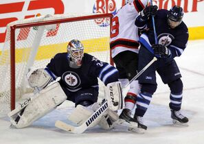 Jets' blue-liner Zach Bogosian clears Devils' centre Travis Zajac from in front of Winnipeg goalie Michael Hutchinson Tuesday night.
