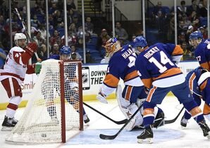 Detroit Red Wings right wing Luke Glendening, left, New York Islanders goalie Jaroslav Halak, center, and defenseman Thomas Hickey (14) look toward the puck shot by Red Wings left wing Drew Miller (not shown) that scored a goal in the first period of an NHL hockey game on Sunday, March 29, 2015, in Uniondale, N.Y. (AP Photo/Kathy Kmonicek)