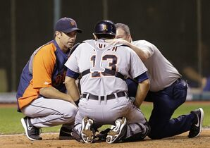 Detroit Tigers manager Brad Ausmus, left, and a trainer talk with catcher Alex Avila after Avila was hit with the ball in the sixth inning of a baseball game, Tuesday, Sept. 2, 2014, in Cleveland. Avila left the game. (AP Photo/Tony Dejak)