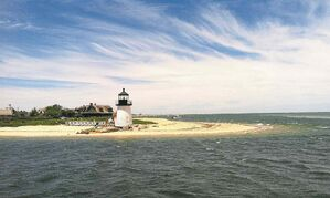 Visitors stand atop the rocks surrounding Brant Point Lighthouse for a view of Nantucket Harbor on Nantucket island.
