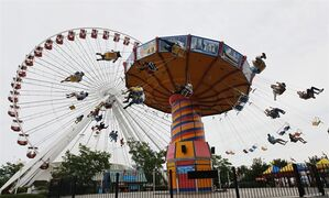 FILE - In this June 13, 2012 photo, visitors ride on the Ferris Wheel and Wave Swinger at Chicago's nearly century-old Navy Pier. Clinton Shepherd, park operations manager at the Navy Pier, rode the tourist spot's Ferris wheel for more than 2 days over the weekend of May 18-19, 2013, bringing the world record for the longest ride to the birthplace of the amusement park favorite. (AP Photo/Charles Rex Arbogast, File)