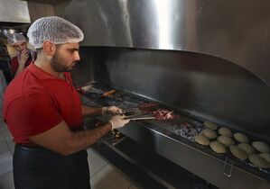 Syrian worker Mohammed, 25, grills kebabs at a restaurant in the northern port city of Tripoli, Lebanon, Thursday, Nov. 20, 2014. Lebanon's health minister revealed that dozens of restaurants, supermarkets and butcher shops across the country were selling food contaminated with sewage and bacteria - and rattled off a long list of beauty clinics that were operating without a license. (AP Photo/Bilal Hussein)