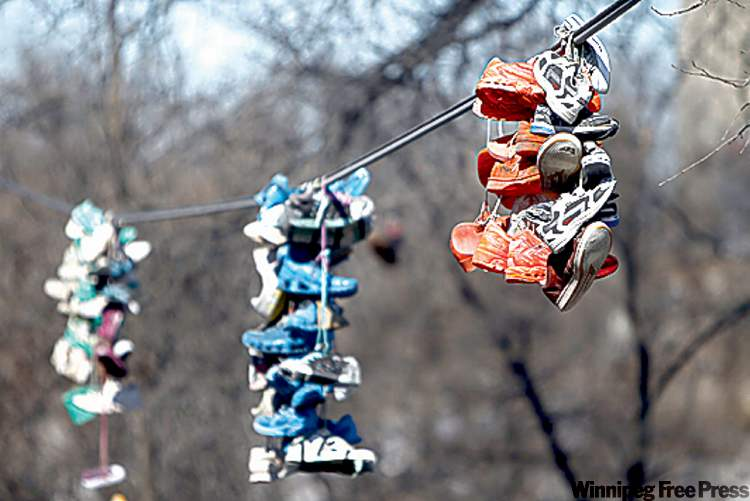 Residents are stumped about the clumps of shoes that hang from nearby wires.