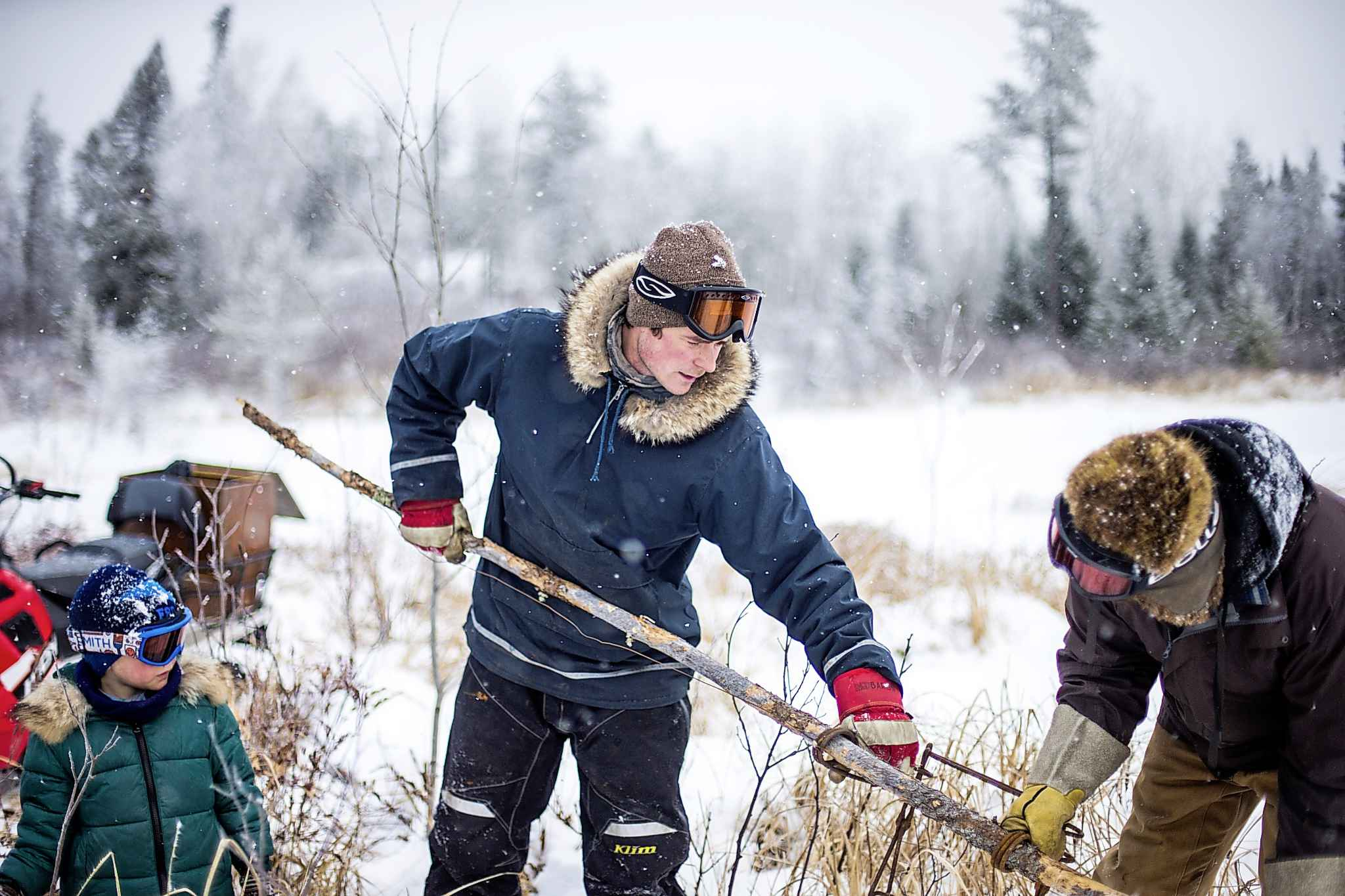 Devin Imrie sets a new beaver trap with help from his dad, Murray, on their trapline near Falcon Lake while Devin's son, Thomas, 5, looks on.